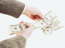 Businesswoman counting hundred dollar bills